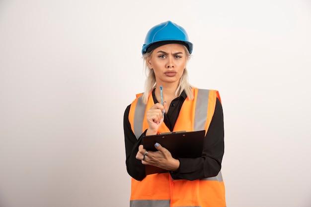 Weiblicher ingenieur, der intensiv auf weißem hintergrund schaut. hochwertiges foto