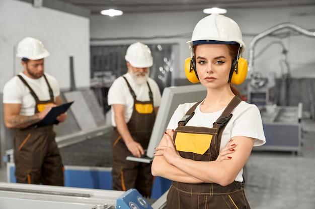 Weiblicher ingenieur, der kamera auf metallfabrik betrachtet