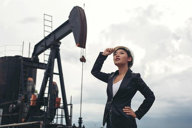 Weiblicher ingenieur, der mit arbeitsölpumpen mit einem weißen himmel steht.