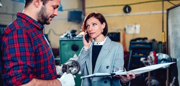 Weiblicher ingenieur, der mit maschinisten steht und am telefon mit kunden spricht