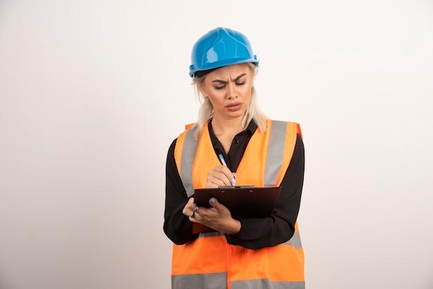 Weiblicher ingenieur, der notizen auf weißem hintergrund prüft. hochwertiges foto