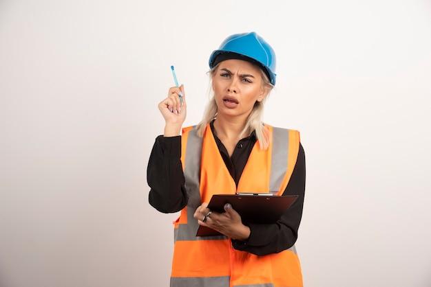 Weiblicher ingenieur, der streit auf weißem hintergrund hat. hochwertiges foto