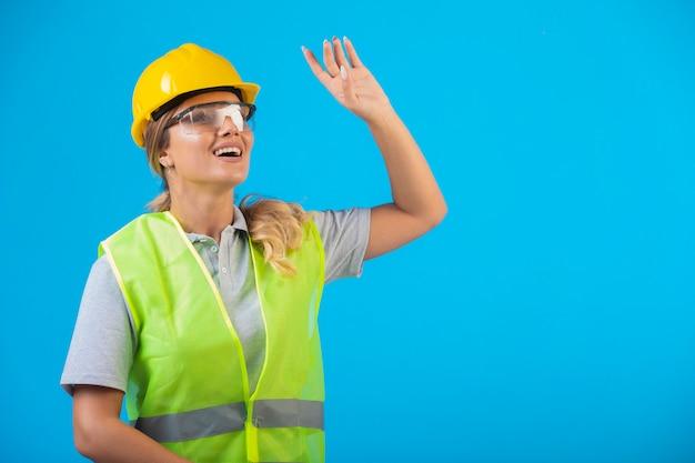 Weiblicher ingenieur im gelben helm und in der ausrüstung, die vorbeugende brillen tragen und nach oben schauen.
