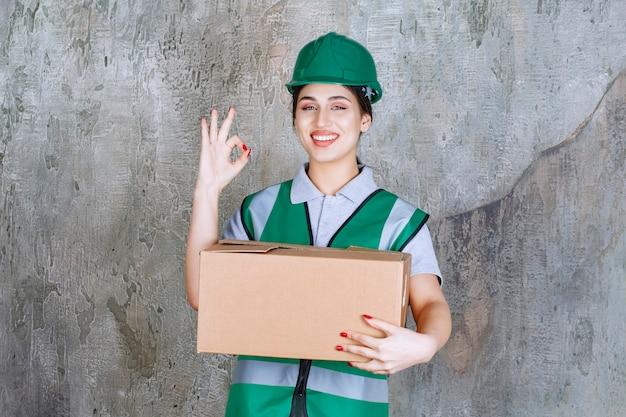 Weiblicher ingenieur im grünen helm, der einen karton hält und zufriedenheitszeichen zeigt.