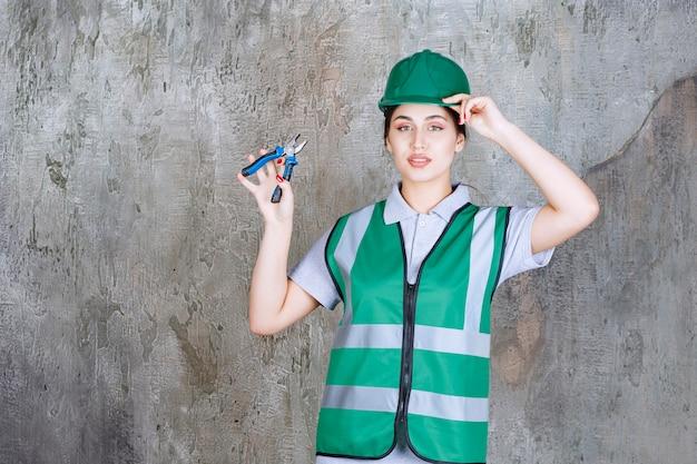 Weiblicher ingenieur im grünen helm, der zangen für eine reparaturarbeit hält.