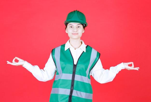 Weiblicher ingenieur im grünen helm und in der uniform, die meditation tun.