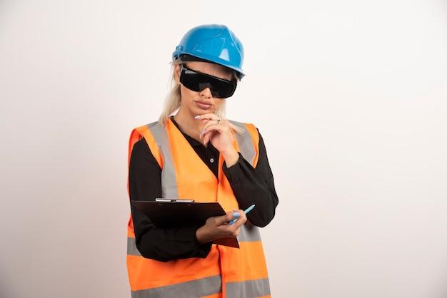 Weiblicher ingenieur in den gläsern, die zwischenablage auf weißem hintergrund betrachten. hochwertiges foto