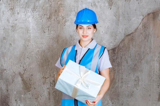 Weiblicher ingenieur in der blauen uniform und im helm, die eine blaue geschenkbox halten.