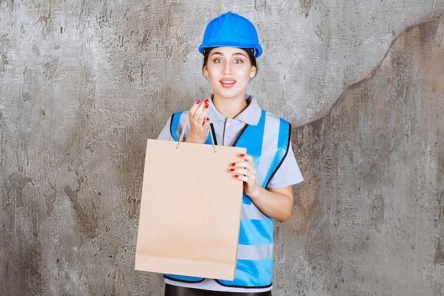 Weiblicher ingenieur in der blauen uniform und im helm, die eine einkaufstasche halten.