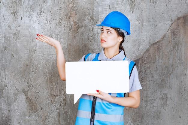 Weiblicher ingenieur in der blauen uniform und im helm, die eine leere rechteckige infotafel halten.