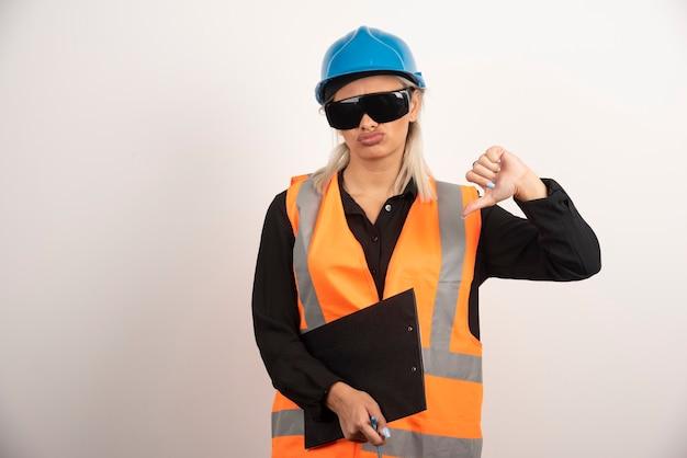 Weiblicher ingenieur in gläsern, die daumen unten auf weißem hintergrund machen. hochwertiges foto