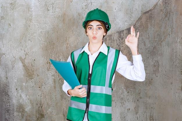 Weiblicher ingenieur in grüner uniform und helm, die einen grünen projektordner halten und positives handzeichen zeigen.