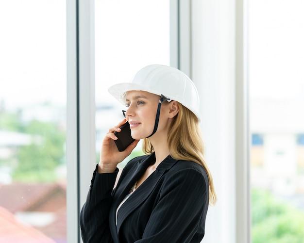 Weiblicher ingenieur macht anruf im bürogebäude