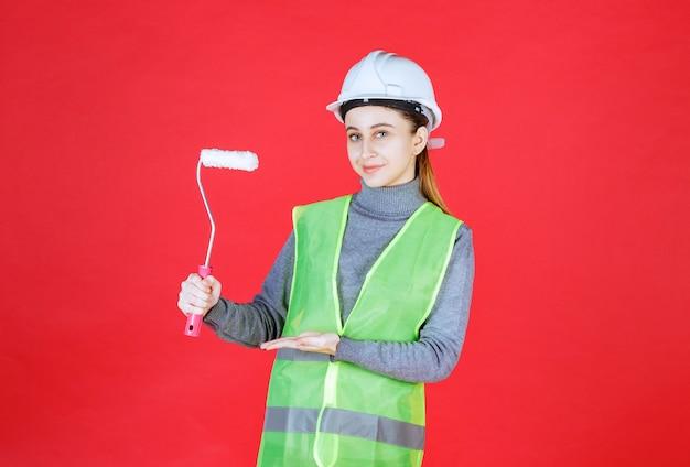 Weiblicher ingenieur mit weißem helm, der eine trimmrolle hält.