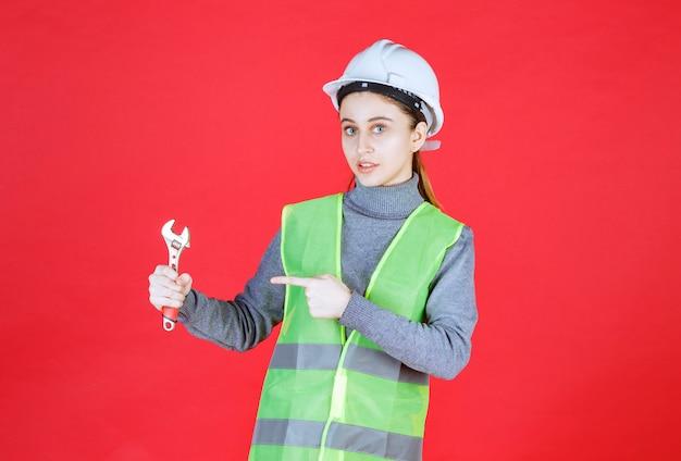 Weiblicher ingenieur mit weißem helm, der einen metallschlüssel hält.