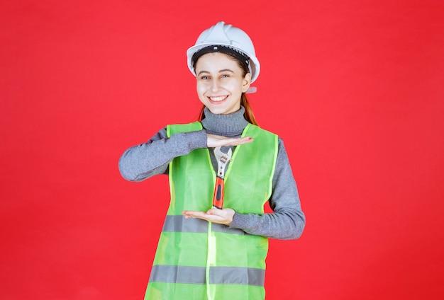 Weiblicher ingenieur mit weißem helm, der einen metallschlüssel hält. Kostenlose Fotos