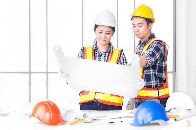 Weiblicher ingenieurblick und mit männlichem ingenieur über drawin besprechen