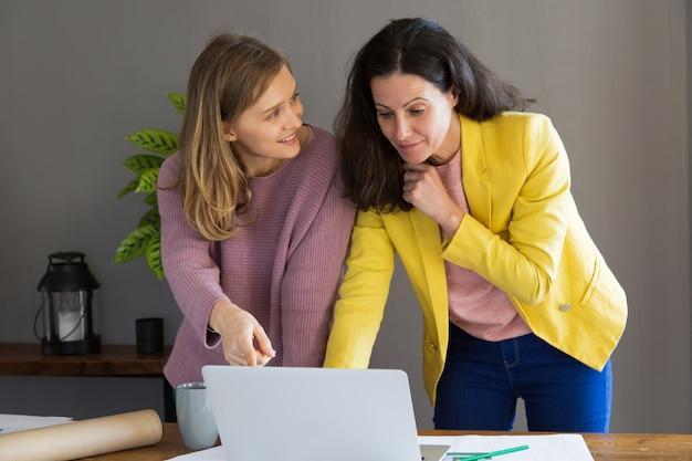 Weiblicher innenarchitekt und kunde, der laptop-computer verwendet
