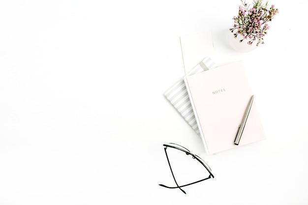 Weiblicher innenministeriumdesktop mit notizbuch, gläsern, stift und wildblumen auf weißem hintergrund spott oben. flache lage, ansicht von oben