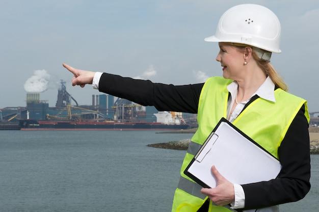Weiblicher inspektor im hardhat und in der sicherheitsweste, die auf industriellen standort zeigen