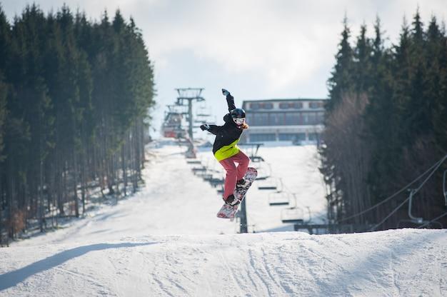 Weiblicher internatsschüler auf dem snowboard, der über die steigung springt