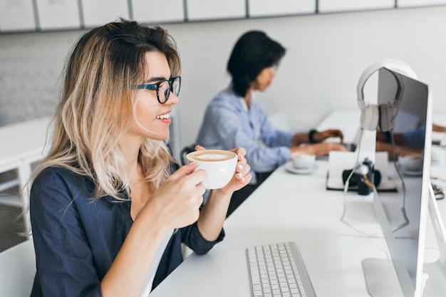 Weiblicher it-spezialist, der computerbildschirm beim kaffeetrinken mit vergnügen betrachtet