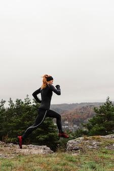 Weiblicher jogger, der über die felsen springt