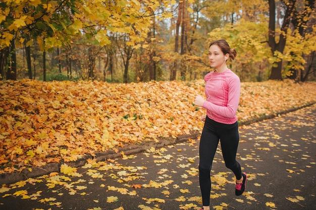Weiblicher jogger läuft auf straße im park. sie ist alleine. modelltraining. es ist herbst draußen.