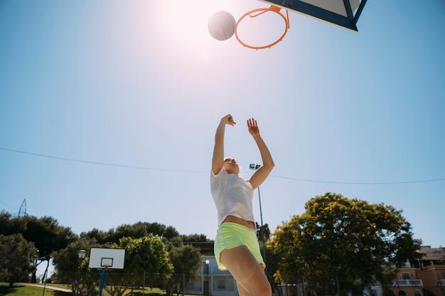 Weiblicher jugendlich student, der basketball am sportsground spielt
