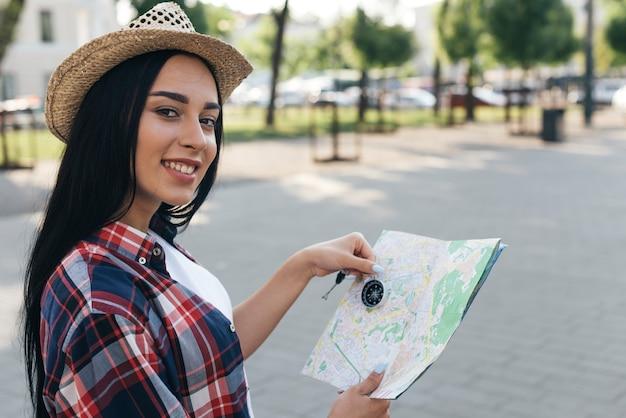 Weiblicher junger reisender, der navigationskompass und karte beim betrachten der kamera hält