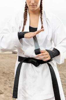Weiblicher kämpfer im karetekostüm im freien