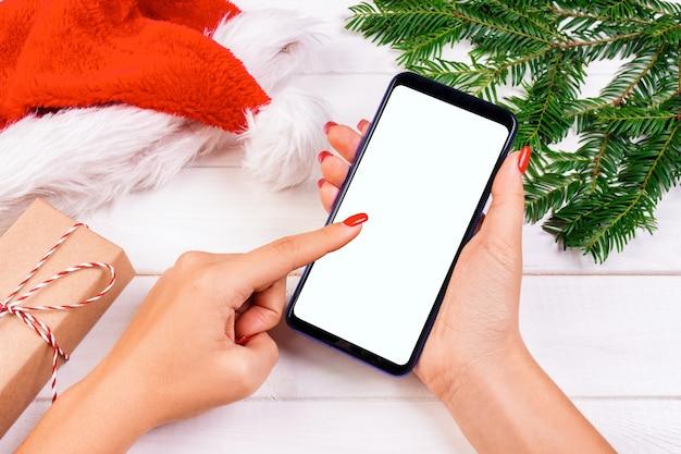 Weiblicher käufer macht bestellung am schirm von smartphone mit kopienraum. winterferien verkauf. online-weihnachtseinkäufe.