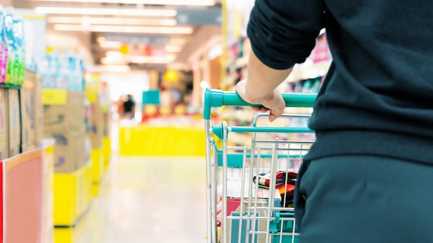Weiblicher käufer mit wagen mit unscharfer bewegung des supermarktkaufhauses