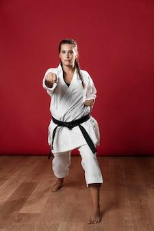 Weiblicher karatekämpfer, der den durchschlag lokalisiert auf rotem hintergrund durchführt