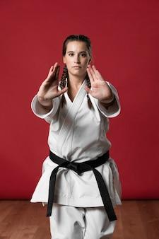 Weiblicher karatekämpfer, der hände ausdehnt und kamera betrachtet