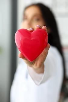 Weiblicher kardiologe, der im roten spielzeugherz der arme hält