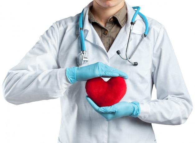 Weiblicher kardiologe in der uniform, die rotes herz lokalisiert hält