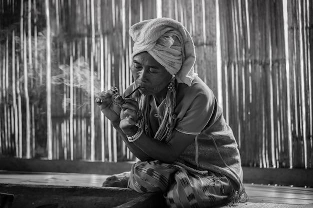 Weiblicher karen-bergvolk raucht die tabakpfeife, die im häuschen traditionell ist