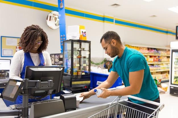Weiblicher kassierer, der barcodes an der registrierkasse liest