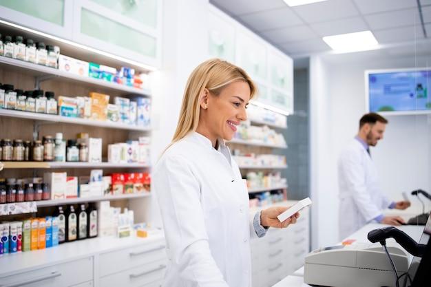 Weiblicher kaukasischer apotheker, der medikamente im apothekenladen verkauft.