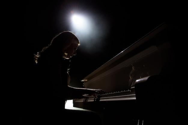 Weiblicher keyboardspieler auf der bühne während des konzerts, hintergrundbeleuchtung.