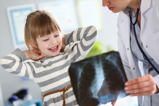 Weiblicher kinderarzt, der mit nettem kleinem mädchen in ihrem büro erklärt diagnose arbeitet