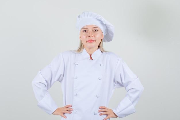 Weiblicher koch, der hände auf taille hält und in der weißen uniform lächelt