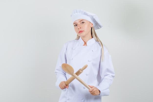 Weiblicher koch, der nudelholz und holzlöffel in der weißen uniform hält und ernst schaut