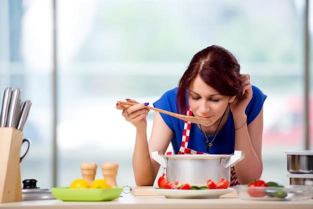 Weiblicher koch, der suppe in hell beleuchteter küche zubereitet