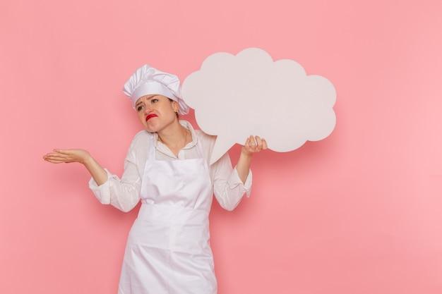 Weiblicher konditor der vorderansicht in der weißen abnutzung, die ein großes weißes zeichen auf dem rosa wandkochküchenküchenlebensmittel hält