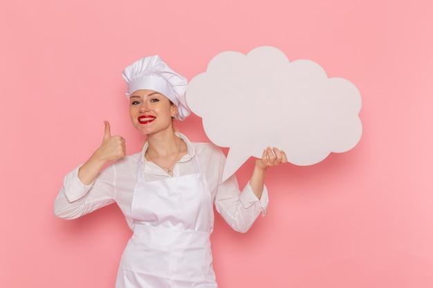 Weiblicher konditor der vorderansicht in der weißen abnutzung, die großes weißes zeichen auf dem rosa wandkochjobküchenküchenlebensmittel hält