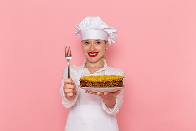 Weiblicher konditor der vorderansicht in der weißen abnutzung, die köstliches gebäck und die gabel hält, die auf dem rosa wand-süßwaren-kochkuchen süß lächeln