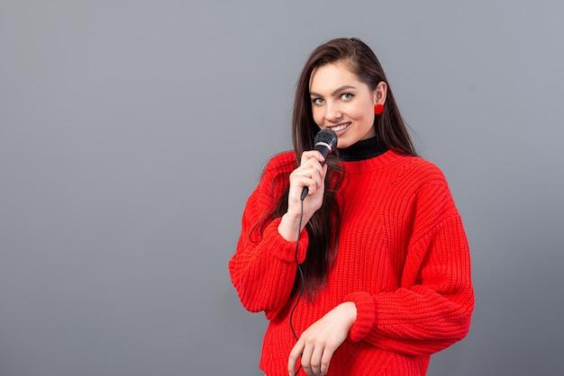 Weiblicher konferenzsprecher gekleidet in einem roten pullover während der präsentation, die aufmerksamkeit fordert, lokalisiert auf grau