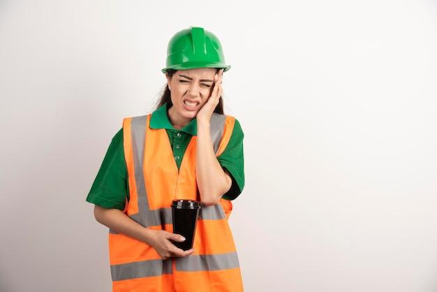Weiblicher konstrukteur mit tasse, die ihren kopf berührt. foto in hoher qualität